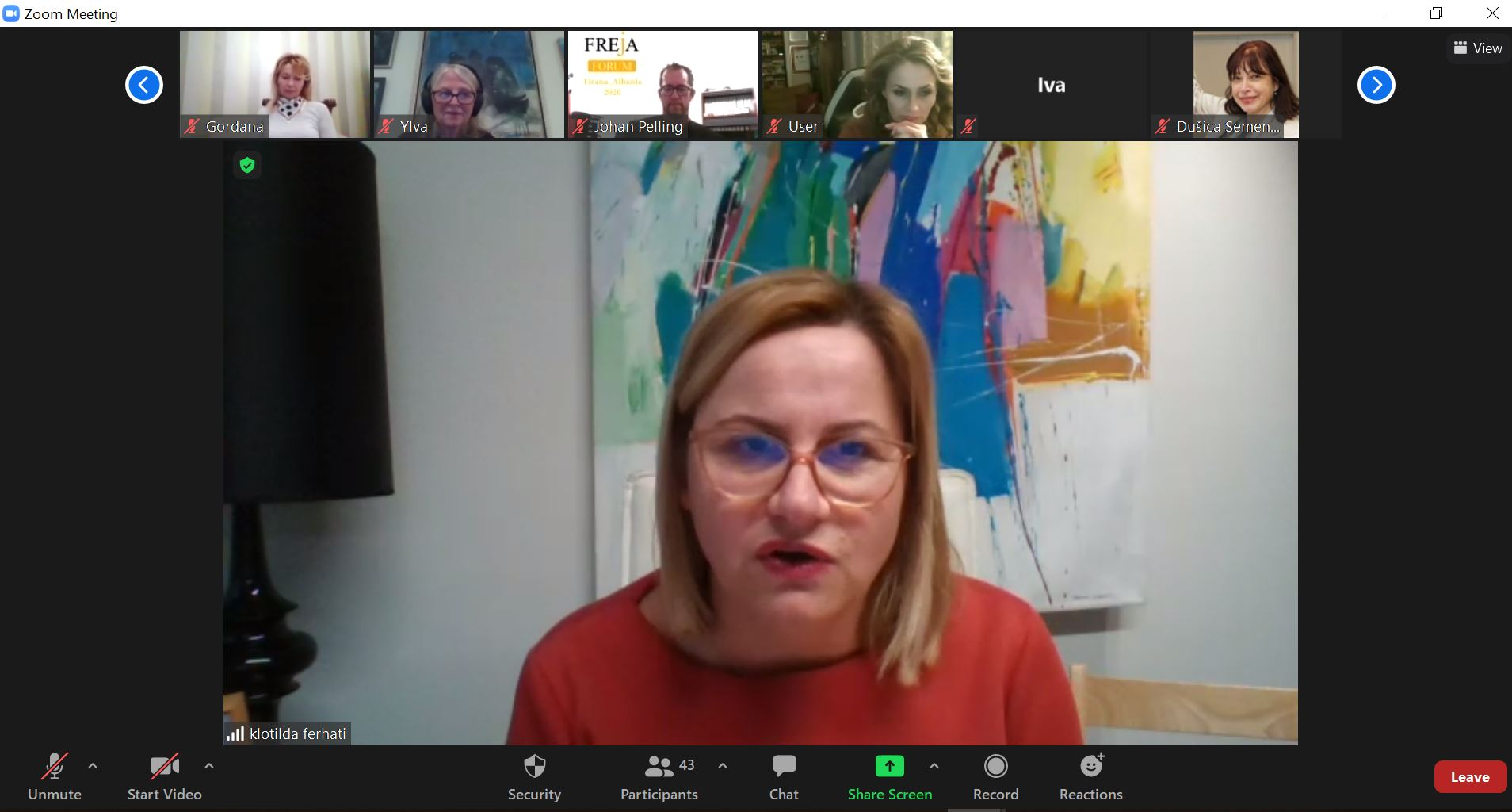 Woman in glasses and red blouse in front of colourful painting, at digital meeting.